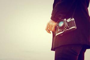 jonge vrouw met een zwarte jas die staat en een retro camera draagt foto