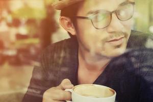 jonge man koffie drinken in café met zonsopgang foto