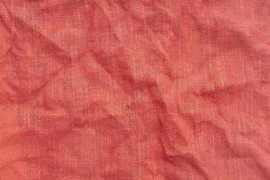 rode jute stof met rimpels achtergrondstructuur. volledig frame foto