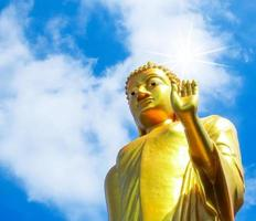 gouden Boeddhabeeld buiten op blauwe hemelachtergrond. foto