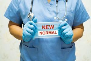 arts met masker met nieuwe normale tekst na covid-19 coronavirus foto
