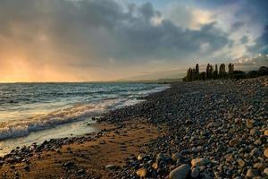 zeegezicht met een prachtige zonsondergang op de achtergrond van de zee foto