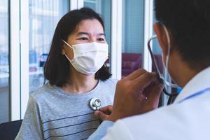 dokter gebruikt stethoscoop om patiënt te onderzoeken die op de polikliniek komt foto