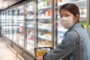 jonge aziatische vrouw die masker draagt dat voedsel in supermarkt winkelt foto