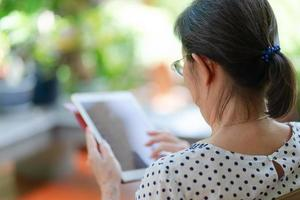 senior aziatische vrouw die tablet gebruikt om sociale media in huistuin te spelen foto