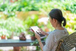 senior aziatische vrouw die tablet gebruikt om sociale media in de tuin te spelen. foto