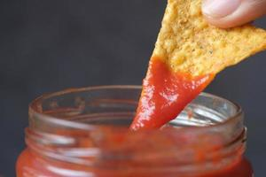 chips die in saus onderdompelen tegen zwarte achtergrond foto
