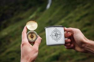 thee in een toeristische metalen mok en een kompas in de hand natuurlijke achtergrond foto
