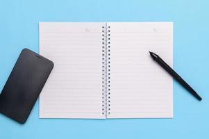 elektronische pen, smartphone, boek, koffiemok op een blauwe achtergrond. foto
