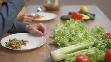close-up eten in schotel en hand van mensen. stel dat salade eet foto