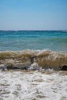 heldere zee en golven aan de kust in de zomer foto