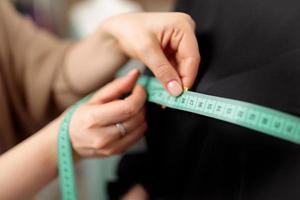 een centimeter is een kleermaker om te meten tijdens het naaien. een centimeter is een hulpmiddel voor het meten van afmetingen. een meter voor het naaien van kleding. maatwerk voor de kleermaker. mensenhanden. foto