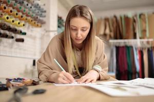 jonge vrouwelijke kunstenaar modeontwerper trekt schets aan tafel in moderne studio. klein kleermakersbedrijf foto