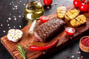 ribeye steak met aardappelen, uien en cherrytomaatjes foto