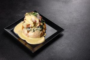 Eggs Benedict of Eggs Florentine op een zwarte plaat in het café foto