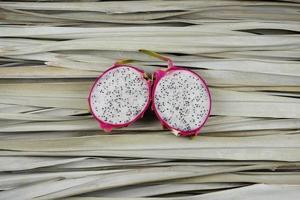 plakjes drakenfruit, gesneden, voor de helft op palmbladeren. foto