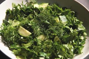 Salade met dille en peterseliekomkommers op plaat een grijze achtergrond foto