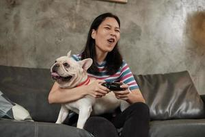 jonge vrouw speelt videogameconsole met haar schattige hond. foto