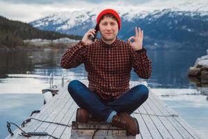 reiziger man praten op mobiele telefoon zittend op houten pier foto