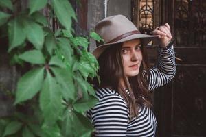 mooie vrouw in een gestreept shirt die haar hoed vasthoudt foto