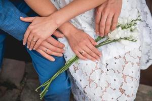 handen van de bruid en bruidegom liggen op een boeket bloemen foto