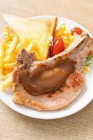 karbonade steak met chips en mini salade op witte plaat on foto