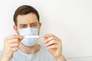 een man meet de temperatuur. warmte. in het masker. foto