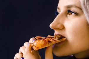 meisje dat pizza eet. geen gezonde voeding. levering aan huis. foto