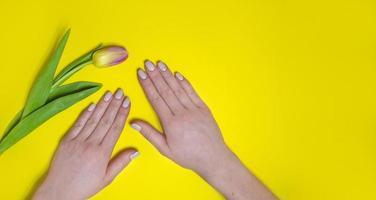 vrouwelijke manicure op een lichte achtergrond. geel foto