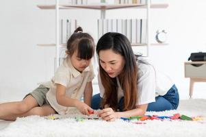 Aziatische moeder leert haar jonge kind thuis puzzels te spelen foto