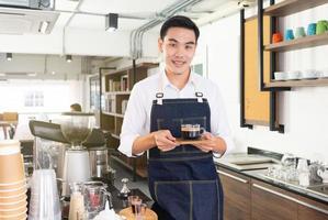 jonge Aziatische barista bereidt hete espresso om de klant in het café te bedienen foto