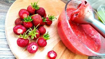 blender in een glazen schaal met aardbeienpuree foto