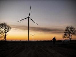 silhouet van een man gaat naar zonsondergang in de richting van windturbines foto