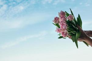 een boeket roze bloemen in een hand tegen de blauwe hemelachtergrond foto