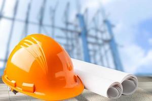 oranje bouwhelm met blauwdruk, ingenieur veiligheidsconcept. foto