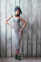 mooie vrouw in grijze jurk en blauwe hoofddoek op een Afrikaanse manier foto