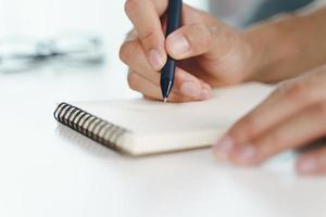 man handen gebruiken pen schrijven op het notitieblok op tafel foto