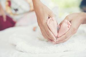 newbron baby voeten in de handen van de moeder. foto