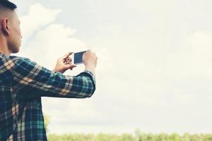 jonge hipster man met smartphone die de landschapsfotografie neemt. foto