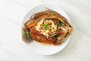gebakken zeebaarsvis met vissaus en pikante salade foto