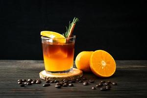 een glas iced americano zwarte koffie en een laagje sinaasappel- en citroensap gedecoreerd met rozemarijn en kaneel foto