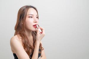 portret mooie aziatische vrouw die rode lippenstift op een witte achtergrond verzint en gebruikt foto