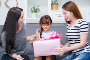 blij van familie met moeder die dochter cadeau geeft op verjaardag. foto