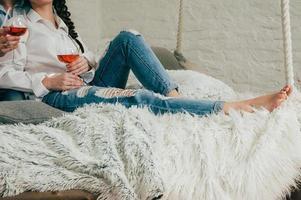 een jong stel in spijkerbroek met wijn op een bed foto