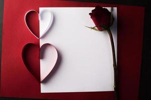 rood hartpapier en blanco met notitiekaart op rode achtergrond. foto