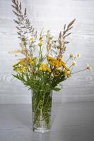 een boeket van wilde bloemen in een glazen vaas op een houten achtergrond foto