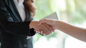 close-up van zakenmensen die handen schudden en de vergadering afronden foto