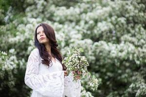 portret van een mooie jonge vrouw in het park in bloeiende takken foto