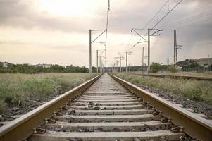 spoorwegmening tijdens de zonsondergang. spoorlijn die naar het oneindige leidt. foto