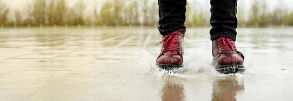 vrouw die in de regen speelt, in plassen springt met spatten foto